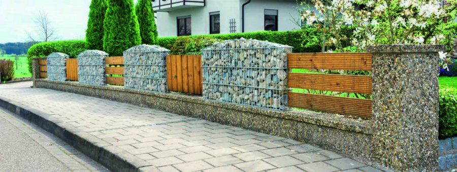 Ogrodzenia posesji wykonane z drewna są wciąż bardzo modne. Można je układać w różnorodne wzory, łączyć z różnymi materiałami. Jest wiele możliwości. Naturalne elementy drewniane i gabiony to dość niespotykane zastosowanie, ale jakże efektowne. Może dlatego, że kosze wypełnione kolorowymi kamieniami – chociaż coraz bardziej popularne – są w naszym kraju jeszcze rzadkością? Zaletą takiego połączenia jest uniwersalność. Parkan pasuje zarówno do ogrodów nowoczesnych, jak i wiejskich. Łatwo go dopasować do otoczenia. Wszystko zależy od tego, czym wypełnimy kosze (możemy w nich umieścić praktycznie wszystko, co będzie stanowiło dekorację) oraz jaki kolor nadamy drewnu. Możemy więc wykazać się kreatywnością. Jeśli wzory i kolorystyka ogrodzenia nam się znudzą, wystarczy, że wymienimy wypełnienie na zupełnie inne oraz pomalujemy drewniane elementy.