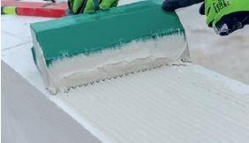 Kielnia o szerokości dostosowanej do szerokości muru ułatwia rozprowadzenie zaprawy.