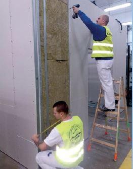 Prace przy konstrukcji ścianki działowej wypełnionej wełną skalną Rockwool. Wkręcanie wkrętów i domierzanie szerokości płyty przed jej docięciem.