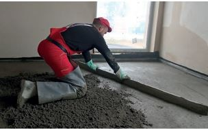 Rozprowadzanie jastrychu cementowego metalową łatą.