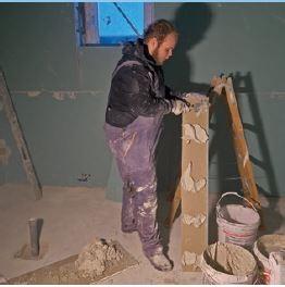 """Obudowa ściany konstrukcyjnej na tzw. klejonkę. Pracownik nakłada """"placki"""" z kleju na docięty fragment płyty konstrukcyjnej."""