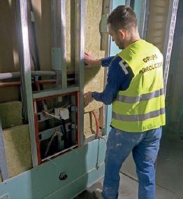 Zabudowa wodoodporną płytą g-k ścianki instalacyjnej w toalecie. Pracownik układa wełnę skalną w celu poprawienia izolacyjności akustycznej ścianki.