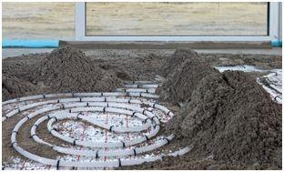 Układanie jastrychu cementowego (konsystencja półsucha) na rurkach ogrzewania wodnego.