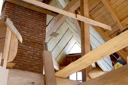 Widok na część dachu podczas prac. Widoczne deskowanie na jeszcze nieocieplonej połaci oraz fragmenty ocieplone wełną szklaną