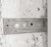 Kotwy montażowe mocuje się do ościeża kilkoma wkrętami. Na koniec powierzchnię ściany należy otynkować lub zakryć płytami gipsowo-kartonowymi.